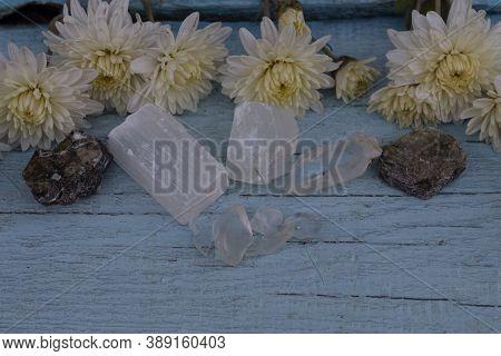 White Chrysanthemums Lie On A Blue Background. Nearby Are Semi-precious Stones Selenite, Apophyllite