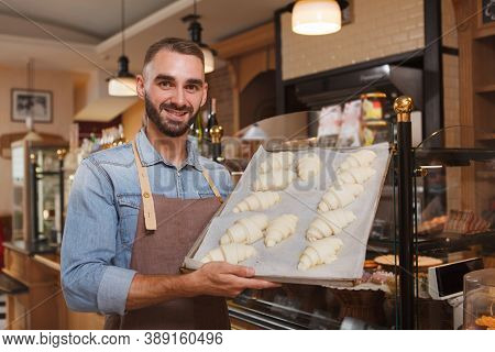 Cheerful Male Baker Holding Tray Of Raw Croissants Ready For Baking