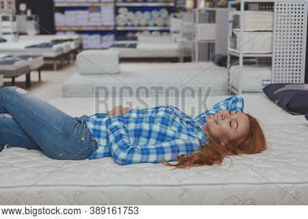 Gorgeous Long Haired Woman Lying On A New Orthopedic Bed At Furniture Store, Copy Space. Attractive