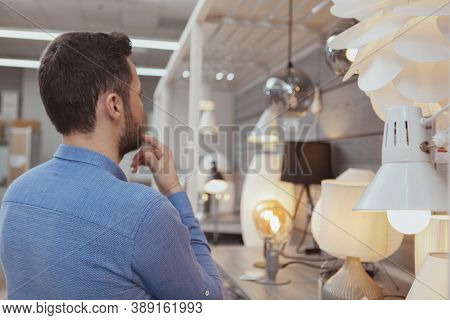 Rear View Shot Of A Male Customer Choosing Lighting For His Apartment At Department Store, Copy Spac