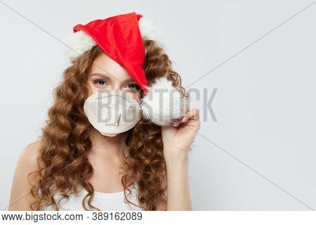 Happy Woman In Santa Hat And Protective Medical Mask. Christmas And New Year Party With Covid-19 Pan