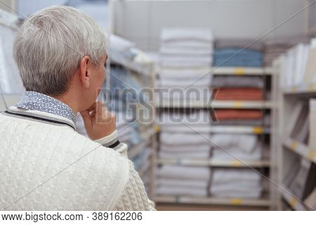 Rear View Cropped Shot Of A Senior Man Looking Thoughtfully At Stacked Textile And Linen At Home Goo