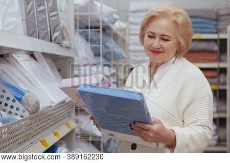 Lovely Senior Woman Smiling, Choosing Linen For Her Home At Furnishings Store, Copy Space