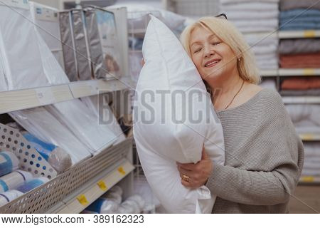 Lovely Mature Woman Smiling With Her Eyes Closed, Trying Soft Pillow At Furnishings Store. Happy Fem