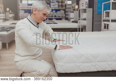 Elderly Male Customer Trying Orthopedic Mattress At Furniture Store, Copy Space. Senior Man Choosing