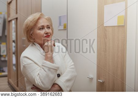 Senior Woman Looking Thoughtful, Shopping For Furniture At Home Department Store. Lovely Elderly Fem
