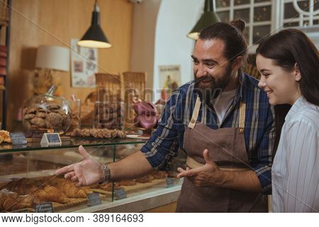 Bearded Mature Baker Helping His Customer Choosing Pastry From The Display. Beautiful Happy Woman Sh