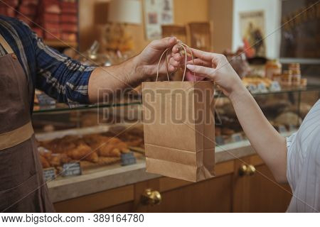 Cropped Shot Of A Male Baker Wearing Apron Giving Paper Shopping Bag To Female Customer, Copy Space.