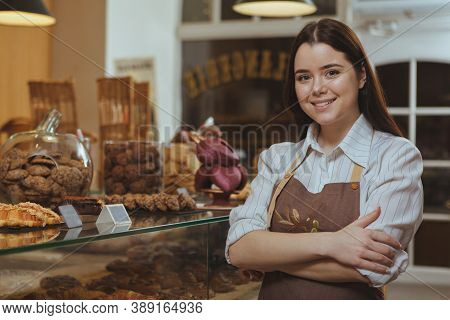 Charming Young Female Baker Smiling To The Camera, Posing Proudly At Her Own Bakery Cafe. Happy Fema