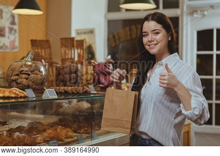 Beautiful Happy Woman Showing Thumbs Up, Shopping At Bakery With A Bag In Her Hand. Attractive Femal