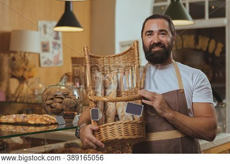 Happy Handsome Bearded Baker Wearing Apron, Carrying Basket With Fresh Delicious Bread, Copy Space.