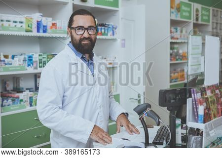 Cheerful Mature Male Druggist Smiling Joyfully To The Camera, Standing Behind Checkout Counter At Hi
