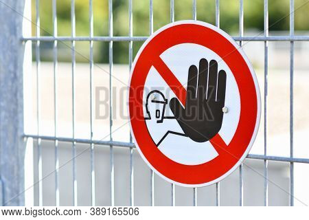 Round 'keep Out' Warning Sign With Person Holding Up Hand In Red Circle At Fence Protecting Construc