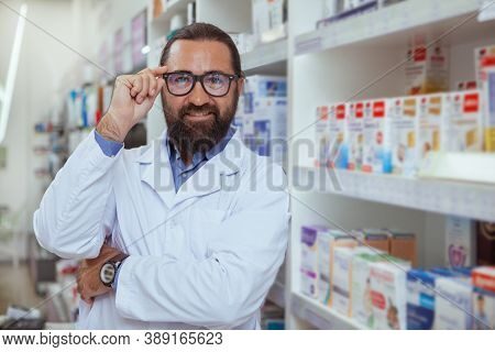 Friendly Mature Male Pharmacist Smiling To The Camera, Putting On His Glasses, Working At The Drugst