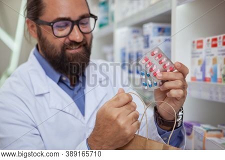 Close Up Cropped Shot Of A Bearded Handsome Mature Pharmacist Selling Prescription Drugs, Putting Pi