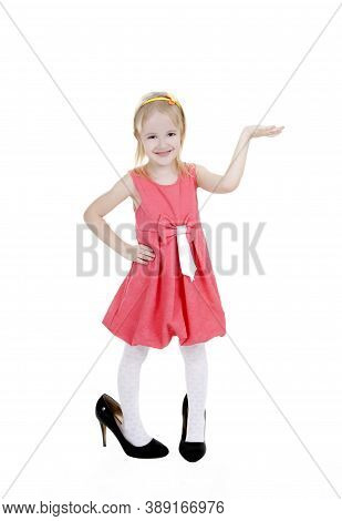 Cute Child Have Fun And Indulges. Blond Little Girl Pointing To Something.