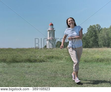 Happy Caucasian Woman Running To A Viewer. Green Meadow And Old White Lighthouse On The Background.