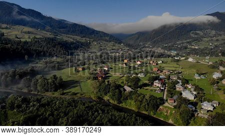 Village In The Mountains Aerial View. Topview Of Many Houses In Mountain Valley.