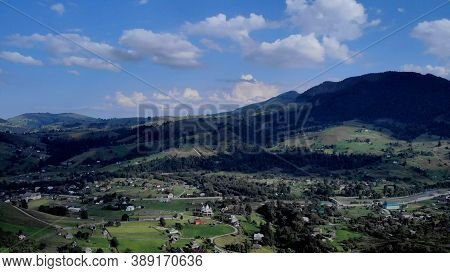 Topview Of Village In Mountains. Beautiful Landscape With Lots Of Huts And Gorgeous Mountains Around