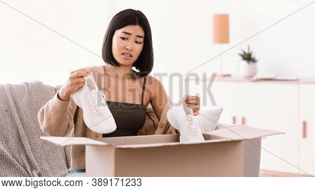 Wrong Item Concept. Confused Frustrated Asian Woman Sitting On Sofa With Cardboard Box, Holding Mist