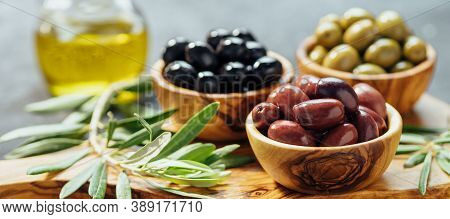Set Of Green, Red And Black Olives And Olive Oil On Gray Background. Different Types Of Olives In Ol