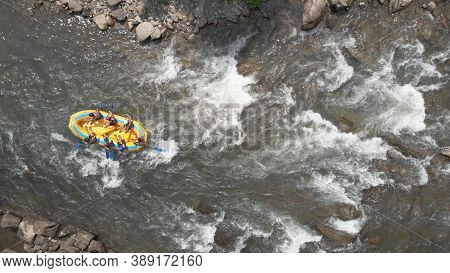 Topview Of People In A Boat. Seething Flows Of River Water.