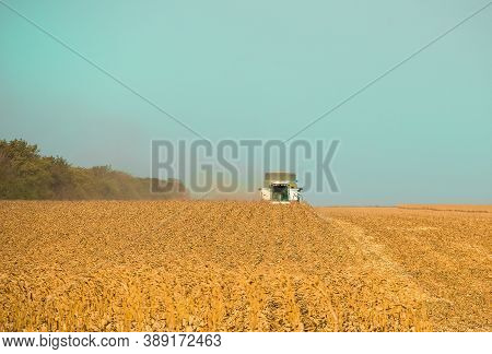 Combine Harvester In A Rural Field During The Day Harvesting