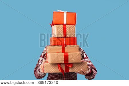 Young Woman Holding Stack Of Gift Boxes Over Blue Studio Background. Unrecognizable Millennial Lady