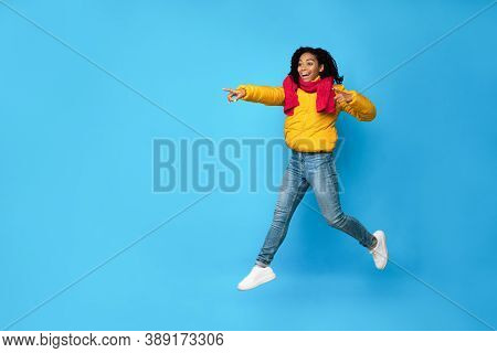 Look There. Excited African American Lady Pointing Fingers Jumping In Mid-air Posing Over Blue Studi