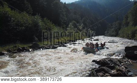 People Dressed In Life Vests Are Rowing With Oars. Rafting On A River. Brave Athletes Racers On A Sp