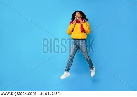 Excited Black Woman In Winter Jacket Jumping In Mid-air Looking Aside Posing Over Blue Studio Backgr