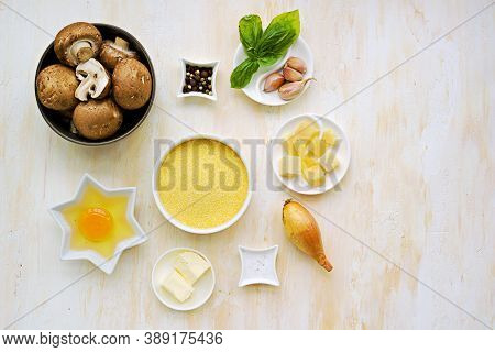 Prepared Ingredients For Cooking Polenta With Fried Mushrooms And An Egg On A Light Concrete Backgro