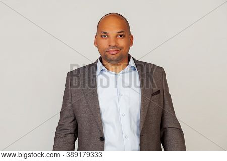 Young Male African American Businessman Attractively Grinning, Smiling, Looking At The Camera With A