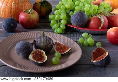 Ripe Fresh Figs, Grapes, Apples And Pumpkins On A Table With A Wooden Surface. Harvest, Autumn Fruit