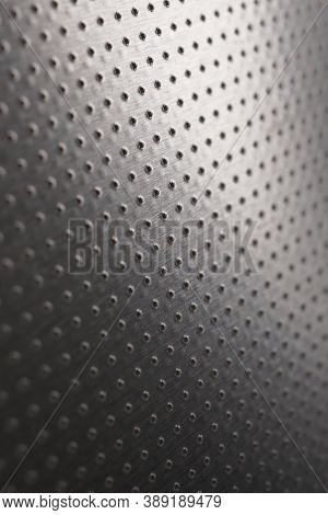 Dark Vertical Industrial Wallpaper Or Background. Perforated Aluminum Surface With Many Holes. Abstr