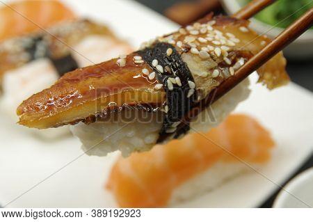 Japanese Cuisine: Unagi Nigiri, Salmon Nigiri, Shrimp Nigiri. Wooden Sushi Sticks