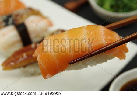 Japanese Cuisine: Salmon Nigiri, Unagi Nigiri, Shrimp Nigiri. Wooden Sushi Sticks