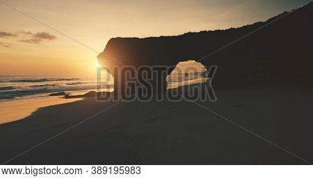 Sunlight silhouette of hole at rocky wall on sand ocean coast. Aerial view of Bawana Beach tourist attraction. Unique geological formation from cliff. Indonesia landmark soft sun set light
