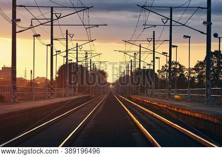 Railway At Beautiful Sunrise. Diminishing Perspective Of Two Empty Railroad Tracks In Station.