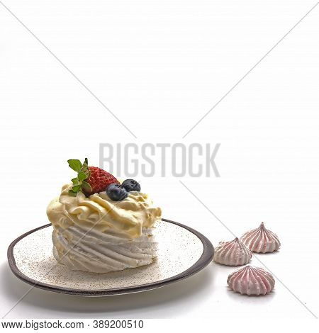 On A White Saucer With A Rim And Dots - Meringue, Decorated With Whipped Cream. On Top Are Strawberr