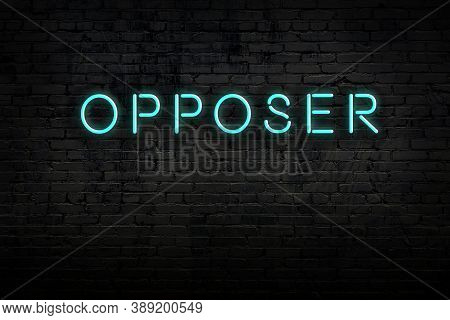 Neon Sign With Inscription Opposer Against Brick Wall. Night View