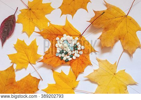 Flatley, Yellow Maple Leaves On A White Background, On A Leaf In The Middle Are Pills. Concept Of In