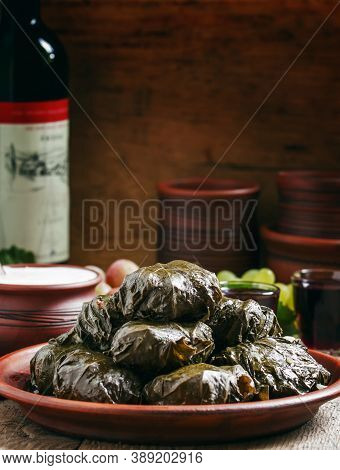 Traditional Greek Dolma With Meat In Grape Leaves, Yogurt Sauce, Grapes And Red Wine On A Clay Dish,