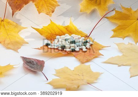 Yellow Maple Leaves, A Handful Of Pills On A Leaf In The Middle. Concept Of Increasing Morbidity In