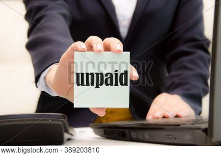 Girl Holding A Card With The Words Unpaid. Financial Loss. Bankrupt. Business Decline
