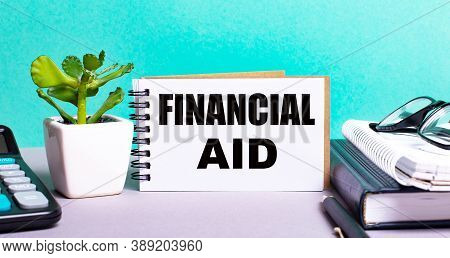 Financial Aid Is Written On A White Card Next To A Flower In A Pot, A Diary And A Calculator On The