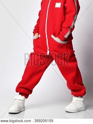 Male Schoolboy Model Showing Underside Red Jumpsuit Part For Camera Standing Over Studio Wall Backgr