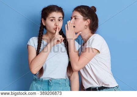 Two Friends Gossiping Isolated Over Blue Background, Girl With Knot Whispering Secret And Keeps Palm