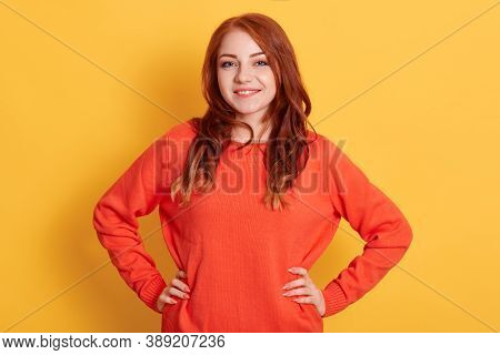 Confident Young Lady With Red Hair Standing With Hands On Hips And Looking At Camera, Being In Good