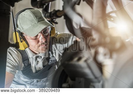 Caucasian Automotive Industry Technician In His 40s Wearing Safety Glasses Looking Into Engine Compa